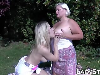 Cute chick hooking up with British GILF in some public space
